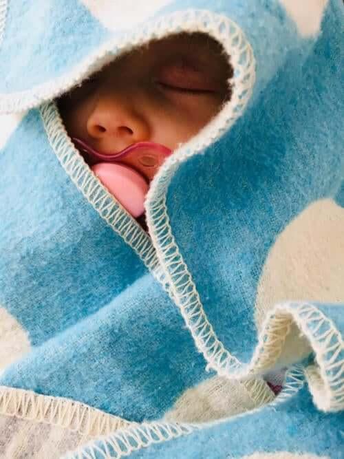 Schlafendes Baby mit rotem Schnuller